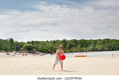 horizontal full length image of a caucasian shirtless man wearing shorts  standing on a sandy beach ready to throw a red beach ball on a hot summer day while on vacation.