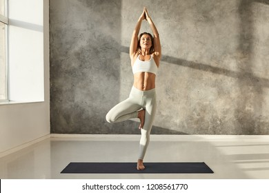 Horizontal full length portrait of attractive young female with beautiful athletic body practicing yoga wearing stylish sports bra and leggings, doing Vrikshasana or Tree yoga pose in large gym