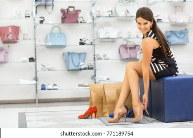 Horizontal full length shot of a gorgeous young woman smiling to the camera while trying on high heels at the local boutique sitting near her shopping bags copyspace consumerism luxury lifestyle