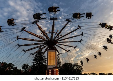 horizontal full lenth silhouette image of people swinging high in the sky on an amusement park ride in the evening with the setting sun.