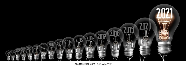 Horizontal group of shining light bulb with fiber in a shape of New Year 2021 and dimmed light bulbs with years passed isolated on black background.
