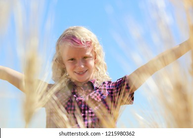 horizontal head shot image of a  blonde young caucasian girl with arms outstretched behind some blurred wheat stalks on a very bright sunny summer day.