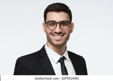 Horizontal headshot of young European Caucasian man in formal clothes isolated on gray background looking through glasses and smiling positively, feeling confident about success in his business
