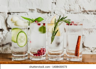 A horizontal image of 4 different refreshing gin and tonics in highball glasses. Cucumber and melon, pomegranate and basil, rosemary and apple, cinnamon and rose pepper. Selective focus.