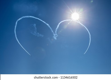 horizontal image of 4 planes in the process of making a heart shape high in the  clear blue sky with a star burst sun shining in the corner.