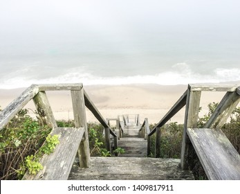 A horizontal image from above of wooden stairs leading to the beach in Nantucket, Massachusetts.