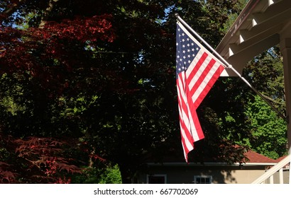 Horizontal image of an American Flag mounted on the side of a house. Off center.