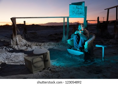 Horizontal image of a Asia-American man in his 30s watching television in desert ruins.