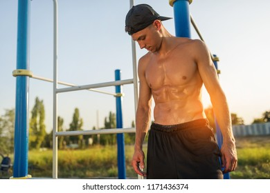 Horizontal image of athlete fitness muscular male relaxing after training on sports ground outdoors. Handsome shirtless sportsman posing against sunset sunlight. People and sport concept.