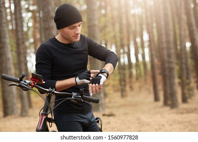 Horizontal image of athletic sportsman using his smartwatch, looking at its screen, touching it, having bicycle walk, leaning on bike, wearing black sportwear, being in autumn forest. Sport concept.