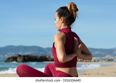 horizontal image of an athletic woman practicing yoga on the beach sand. concept of healthy outdoor life