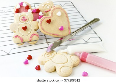 horizontal image of baked heart and teddy bear cookies on a cookie rack decorated by a child with icing.