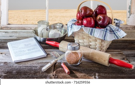 horizontal image of basket of red apples and baking tools and recipe for apple pie.