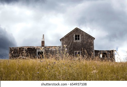 horizontal image of a beautiful old abandoned house full of character sitting under a dark storm cloud with tall dead grass surrounding the home.