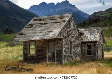 horizontal image of a beautiful old abandoned little wood house with an old washing machine sitting in doorway with mountains looming in the background on a warm summer day.
