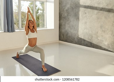 Horizontal image of beautiful young European woman with fit muscular body doing yoga on mat, standing in Warrior One pose which is good for strong legs. Sports and active healthy lifestyle concept