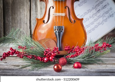 horizontal image of the bottom half of a violin with sheet music and christmas fern and cranberries adorning the front of the fiddle on rustic wood background.