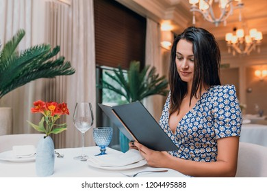 Horizontal image of brunette young elegant woman wearing dress sitting in the restaurant with menu for dinner. Caucasian female posing in cafeteria and waiting her friends.