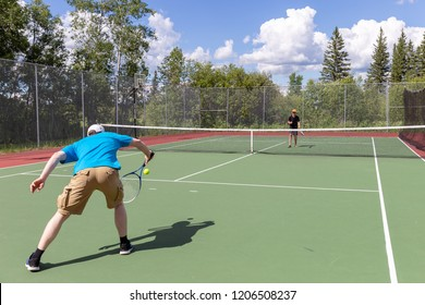 horizontal image of a caucasian father and son playing tennis on the court on a beautiful summer day.