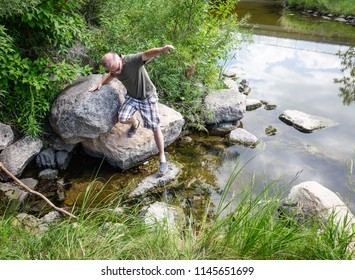 horizontal image of a caucasian male carefully stepping over large rocks by the lake while hiking in the summer time.