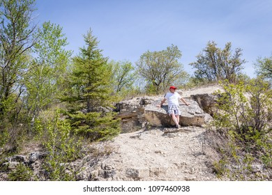 horizontal image of a caucasian man leaning against a large rock while resting while on a hike on a hot summer day.