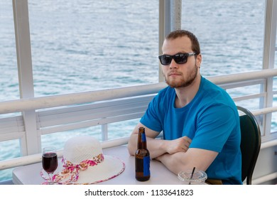 horizontal image of a caucasian man sitting on a houseboat on the lake enjoying a beer on a sunny summer day.