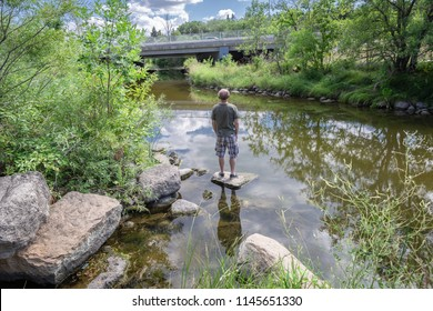 horizontal image of a  caucasian man standing on a rock in the middle of a pond surrounded by green trees in the rural countryside in the summer time.