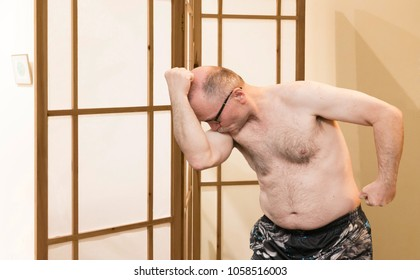 horizontal image of a caucasian older mature man flexing his muscles and kissing his bicep to be  silly.