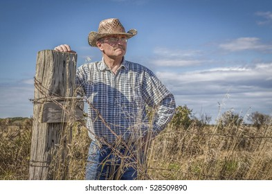 horizontal image of a caucasian white male farmer wearing a cowboy hat standing and leaning against a fence post gazing into the distance on a warm fall day.