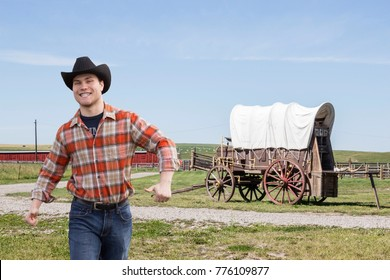 horizontal image of a caucasian white male walking toward the camera with a silly grin on his face with a covered wagon sitting in the pasture in the background in the summer time
