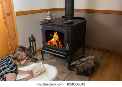 horizontal image of a caucasian woman lying on a white fur rug on the floor reading a book by a wood burning stove.