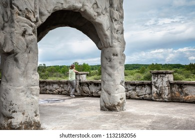 horizontal image of a caucasian woman on vacation leaning against an old stone wall under a big stone archway gazing across the green hills and trees
