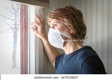 horizontal image of a caucasian woman sadly looking out the window of her home being quarantined due to caronavirus - Shutterstock ID 1679134627