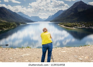 horizontal image of a caucasian woman standing by a lake surrounded by mountains photographing on a warm summer afternoon.