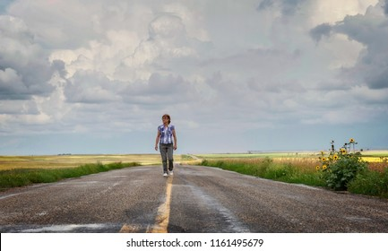 horizontal image of a caucasian woman walking in the middle of the highway just after a rain in the summer time.