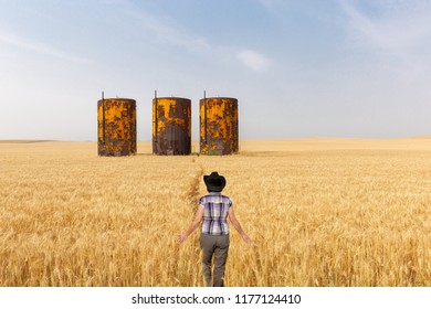 horizontal image of a caucasian woman walking in a wheat field towards oil tanks sitting in the field in the summer time.