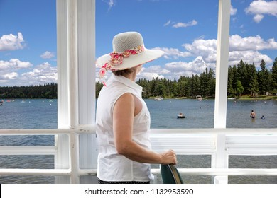 horizontal image of a caucasian woman wearing a big hat on a houseboat on a lake watching people swimming close to shore in the summer time