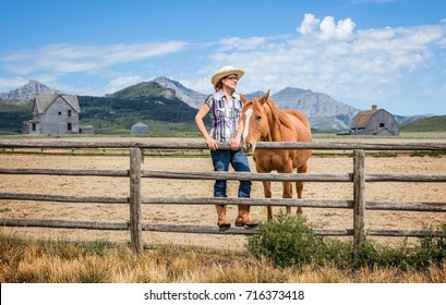 horizontal image of a caucasian woman wearing cowgirl attire standing on the fence pole with her brown horse standing beside with mountains looming in the background on a warm summer day
