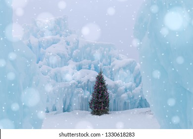 horizontal image of a Christmas tree with twinkling lights sitting in the middle of a dreamy blue ice castle with large blurred snowflakes gently falling in the foreground on a cold winter day.