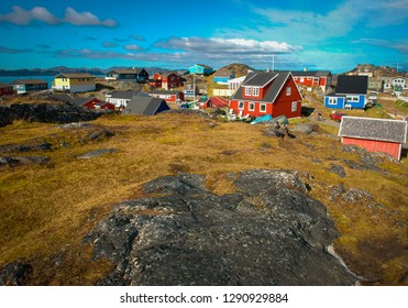 Horizontal image of the colourful houses of Nuuk, capital city of Greenland, Northern Europe, rock covered by green grass in the foreground, no people, sunny day with bright blue sky summer sun