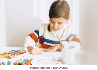 Horizontal image of cute little girl painting withoil pencils, sitting at white desk at home. Pretty artistic preschool child drawing with pencils. People, childhood and education concept