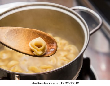 horizontal image with detail of a tortellini on a wooden ladle while cooking in a hot broth