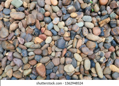 Horizontal image of different kind of colorful pebbles stones wall texture. Abstract nature background of beautiful sand stone floor in garden or park. Sea  cobblestone or river rock stones wallpaper.