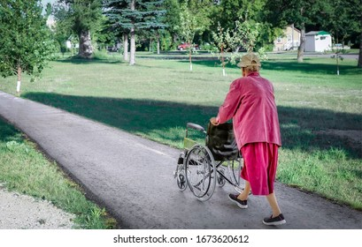 horizontal image of an elderly caucasian lady walking down a paved sidewalk pushing an empty wheelchair on a sunny summer afternoon