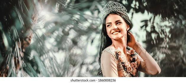 Horizontal image elegant smiling lady with tiara on a head posing in a forest. Young attractive bride photo shooting enjoy photo session on nature. Beauty and fashion photography concept