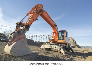 Horizontal image of an excavator (aka rubber duck or digger) in front of a large heap of asphalt.