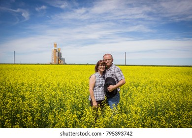 horizontal image of a farm couple standing in a yellow canola field in an embrace posing for the camera on a warm sunny summer afternoon.