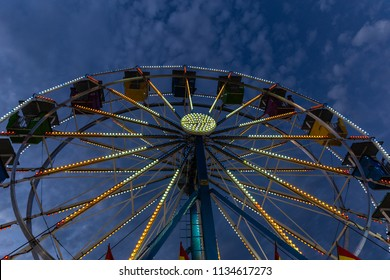 horizontal image of a farris wheel lit up with lights under the dark blue sky at night time with copy space.