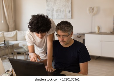Horizontal image of farther and son studying from home using black laptop, with farther sitting in front of the laptop and son standing behind his shoulder and pointing his finger on the screen