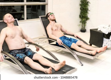horizontal image of a father and  adult son lying on indoor lawn chairs by an indoor swimming pool having a nap and rest.